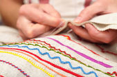 Patterns on fabric and hands sewing — Stock Photo