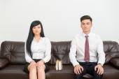 Business couple sitting on sofa in office with present — Stock Photo