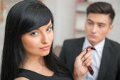 Businesswoman flirting and pulling her colleague by the tie — Stock Photo