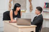 Business couple flirting near the table in office — Stock Photo