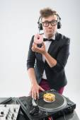 Dj eating donut on working place turntable — Stock Photo