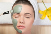 Beautiful girl with a towel on her head applying facial clay mas — Stock Photo