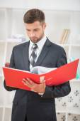 Businessman with red folder — Stock Photo