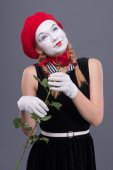 Portrait of female mime with red hat and white face grimacing wi — Stock Photo