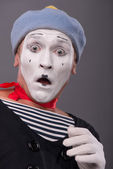 Portrait of young male mime with white face, grey hat showing em — Stock Photo