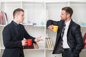 Two businessmen in suits having a coffee-break — Stock Photo