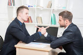 Two angry businessmen armwrestling in office — Stock Photo