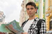 Male traveler  holding a map  and looking aside — Stock Photo