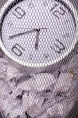 Close-up photo of a clock in refuse bin with other office rubbis — Photo