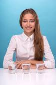 Portrait of girl sitting at the table near a glass with clean wa — Stock Photo