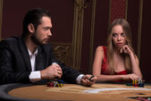 Handsome  man and beautiful woman in casino — Stock Photo