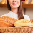 Beautiful young woman at bakers shop — Stock Photo #64999021