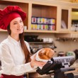 Female baker  stretching out a paper package with bread — Stock Photo #64999213