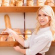 Beautiful young woman in a bakery — Stock Photo #64999551