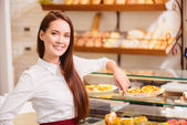 Beautiful young saleswoman in a bakery — Stock Photo