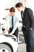 Handsome young man in dealership — Stock Photo