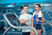 Beautiful girl in sports club with instructor — Stock Photo