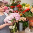Florist puts bouquet into the vase — Stockfoto #68190783