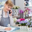 Florist talking over the phone and making notes — Stock Photo #68191205