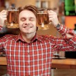 Young man with beer mugs — Stock Photo #68774751