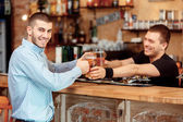 Barman stretches out glasses of beer — Stock Photo