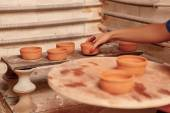 Woman puts clay pots on the shelf — Stock Photo