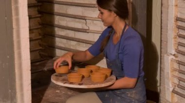 Woman  putting crocks in drying stove — Vídeo de Stock