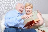 Couple reads a book at home — Stock Photo
