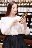 Woman holds a wine bottle in the store — Stock Photo