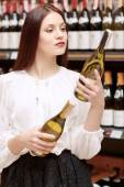 Woman holds a wine bottle in the store — Photo