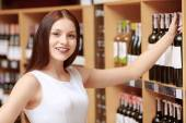 Woman buys wine in a store — Stock Photo