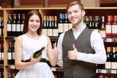 Woman interacts with a sommelier in shop — Stock Photo