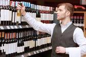 Sommelier in de winkel in de buurt van schappen — Stockfoto