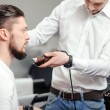 Man shaves his beard with a hair clipper — Stock Photo #70152093
