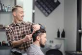Barber cuts hair of a man — Stock Photo