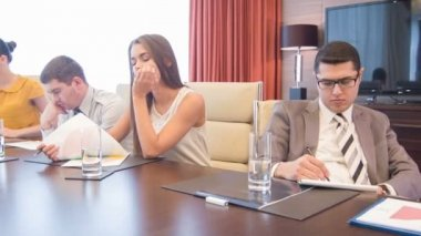 Company of young people sitting in modern light conference hall having tedious time — Stock Video
