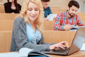 Female student uses laptop — Stock Photo