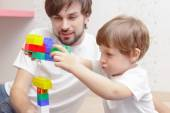 Father and son play with building kit — Stock Photo
