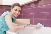 Uśmiechnięta kobieta sprzątanie łazienki — Zdjęcie stockowe