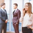 Blond young business woman standing in front of two men talking — Stock Photo #71857767