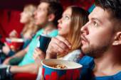 Impressed cinema viewers with popcorn — Stock Photo