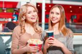 Two girls with coke and popcorn — Stock Photo