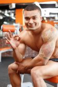 Muscular man sitting in gym and pointing ok — Stok fotoğraf