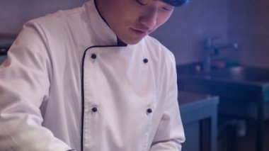 Tracking shot of smiling Asian chef in white uniform — Stock Video