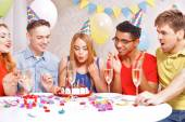 Young people celebrating a birthday sitting at the table — Stock fotografie