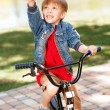 Little smiling boy riding bicycle and pointing upwards — Stock Photo #73459007