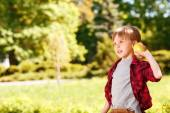 Boy going to throw apple in park. — Stock Photo