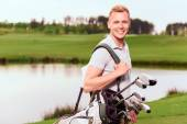 Young smiling man standing on course with equipment — Stock Photo