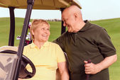 Senior man standing near his wife in cart — Stock Photo