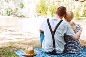 Couple of people sitting on cover and embracing — Stock Photo